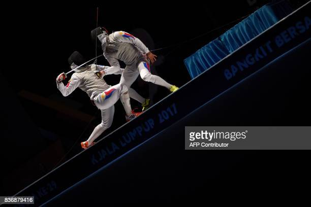 Nathaniel Perez of Philippines competes with compatriot Brennan Wayne Louie in the men's fencing foil individual final of the 29th Southeast Asian...