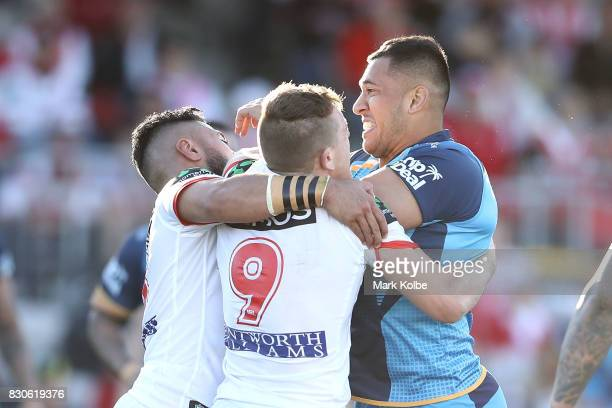 Nathaniel Peteru of the Titans is tackled by Taane Milne and Cameron McInnes of the Dragons during the round 23 NRL match between the St George...