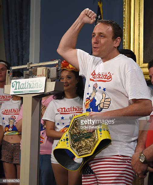 Nathan's Famous hot dogeating champion for 2013 Joey Chesnut holds his belt and pumps his fist at a weighin ceremony on July 3 2014 at City Hall in...