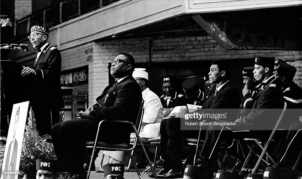 Nation of Islam leader <a gi-track='captionPersonalityLinkClicked' href=/galleries/search?phrase=Elijah+Muhammad+-+Religious+Leader&family=editorial&specificpeople=1311056 ng-click='$event.stopPropagation()'>Elijah Muhammad</a> (born Elijah Poole, 1897 - 1975) speaks from a lecturn during Saviour's Day celebrations at the International Ampitheatre, Chicago, Illinois, February 27, 1966. Among those seated behind him are <a gi-track='captionPersonalityLinkClicked' href=/galleries/search?phrase=Louis+Farrakhan&family=editorial&specificpeople=215023 ng-click='$event.stopPropagation()'>Louis Farrakhan</a> (born Louis Walcott) (left, fore) and boxer <a gi-track='captionPersonalityLinkClicked' href=/galleries/search?phrase=Muhammad+Ali+-+Boxer+-+Born+1942&family=editorial&specificpeople=93853 ng-click='$event.stopPropagation()'>Muhammad Ali</a> (born Cassius Clay) (next to Farrakhan). Farrakhan wears a Fruit of Islam uniform, a subset of the Nation of Islam.