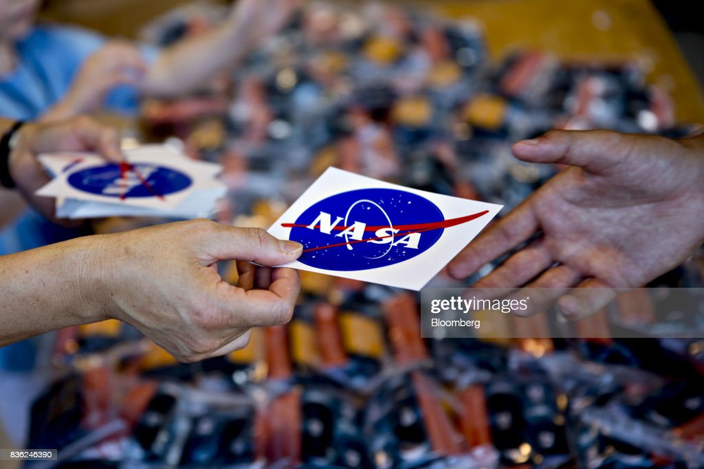 National Aeronautics and Space Administration (NASA) stickers are handed out ahead of a solar eclipse viewing event on the campus of Southern Illinois University (SIU) in Carbondale, Illinois, U.S., on Monday, Aug. 21, 2017. Millions of Americans across a 70-mile-wide (113-kilometer) corridor from Oregon to South Carolina will see the sky darken as the sun disappears from view, albeit for only a few minutes at a time. Photographer: Daniel Acker/Bloomberg via Getty Images