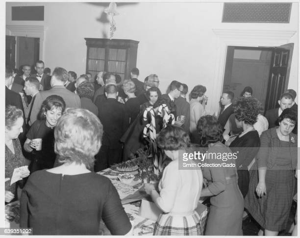 National Archives employees socialize and enjoy refreshments at a Christmas party College Park Maryland December 1962