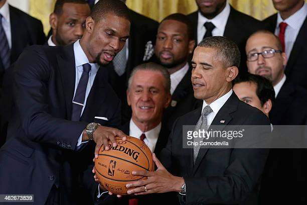 National Basketball Association 20122013 champion Miami Heat player Chris Bosh presents President Barack Obama with a signed basketball during an...