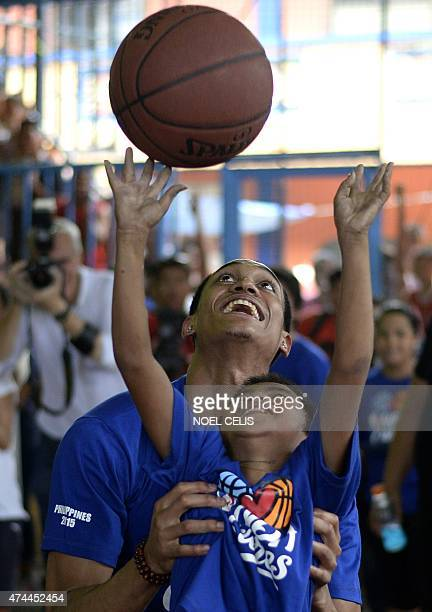 National Basketball Association player Jordan Clarkson from the Los Angeles Lakers lifts a boy to shoot at the basket during a basketball clinic in...