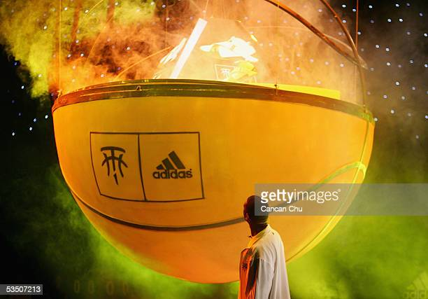 National Basketball Association star player Tracy McGrady of the Houston Rockets looks at a huge basketball during a ceremony to launch an Adidas...