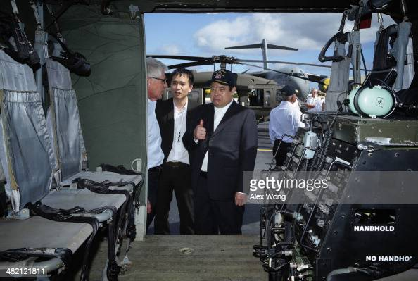 National Defense Minister of Vietnam General Phung Quang Thanh gives a thumbs up as he looks at the interior of a Black Hawk helicopter with US...