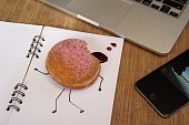 National Donut day Merged mediums A bad day A desktop with a laptop phone and a jam doughnut with a bite taken and jam oozing out on a plain notebook...