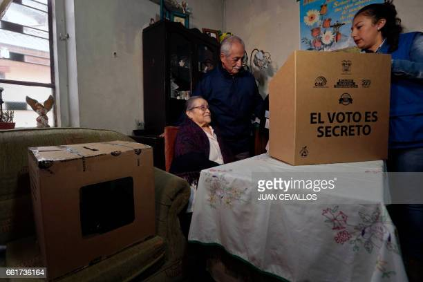 A National Electoral Council staffer assists Blanca Rosas to vote for Ecuador's presidential runoff at her house in the framework of the 'Vote at...