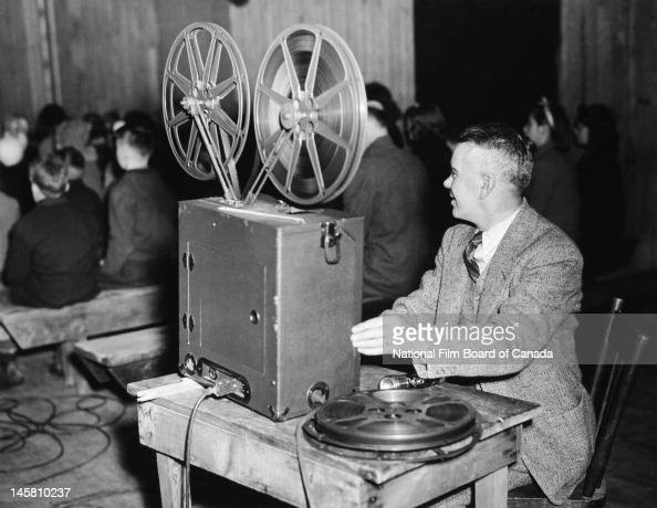 A National Film Board of Canada field representative and traveling projectionist gives a screening for an audience of school children Ontario Canada...
