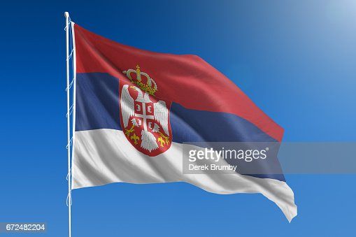 National flag of Serbia on clear blue sky : Stock Photo