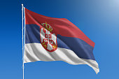 The National flag of Serbia blowing in the wind in front of a clear blue sky