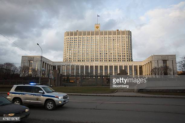 A national flag of the Russian Federation flies from a flagpole above the Russian White House government building in Moscow Russia on Sunday March 16...