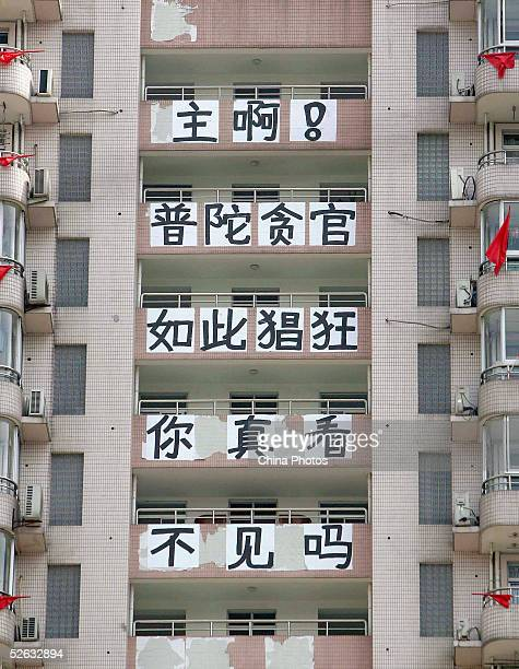 National flags and Slogans reading 'God can't you see the rampant officials corruption in Putuo District' are seen hung outside a residential...