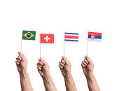 Little paper national flags in hands isolated on white background. Flags of Brasil, Switzerland, Costa Rica, Serbia.