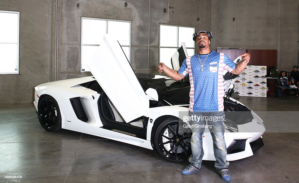 National Football League player Marshawn Lynch poses in front of his 2013 Lamborghini Aventador Roadster equipped with Monster Sound at Findlay...