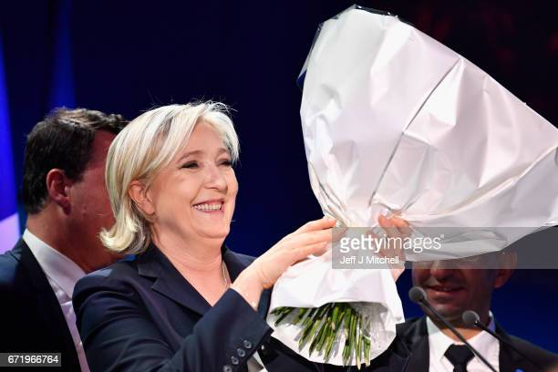 National Front leader Marine Le Pen receives flowers as she addresses activists at the Espace Francios Mitterrand on April 23 2017 in Henin Beaumont...