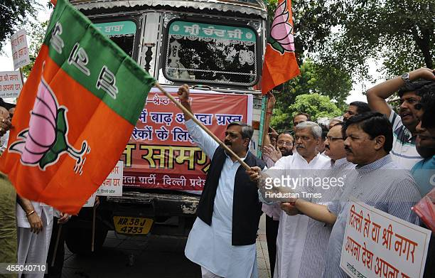 BJP national general secretary JP Nadda Delhi BJP incharge Prabhat Jha Delhi BJP president Satish Upadhyay flag of the trucks carrying relief...