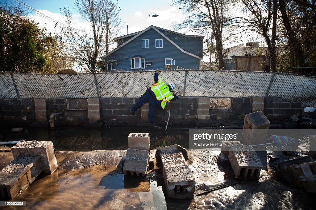 A National Grid employee checks for a gas line along the foundation of a house that was destroyed in the Midland Beach neighborhood of Staten Island on November 3, 2012 in New York City. As clean up efforts from Superstorm Sandy continue, colder weather and another storm predicted for next week are beginning to make some worried.