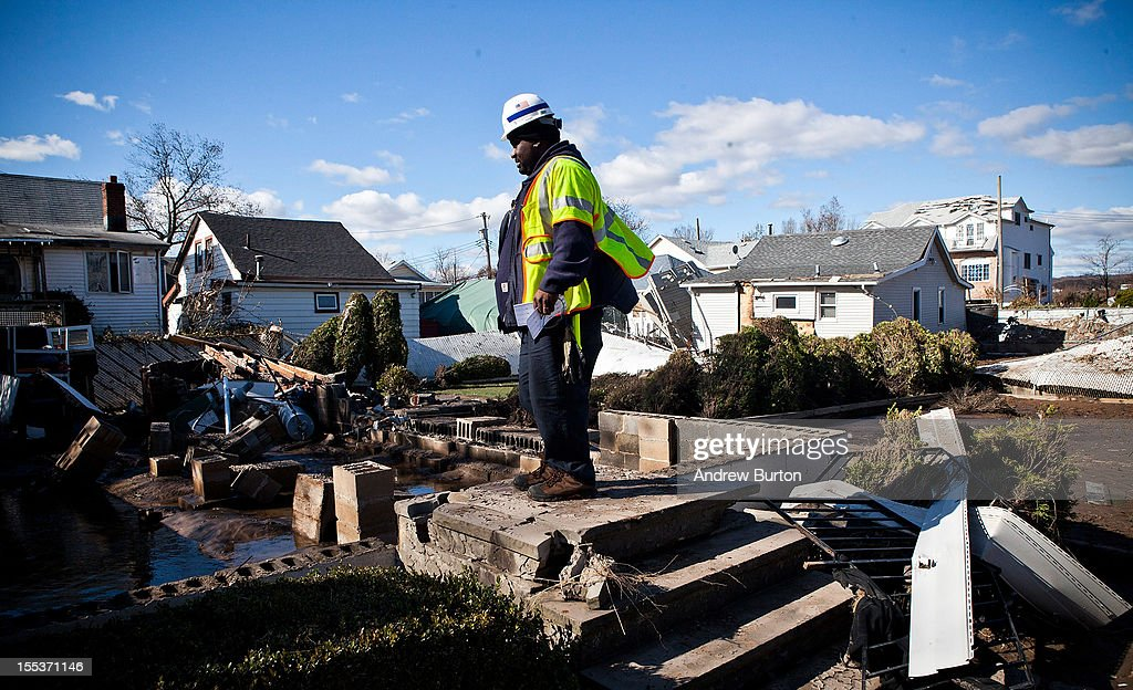 A National Grid employee stands on the front steps of where a house once stood in the Midland Beach neighborhood of Staten Island on November 3, 2012 in New York City. As clean up efforts from Superstorm Sandy continue, colder weather and another storm predicted for next week are beginning to make some worried.