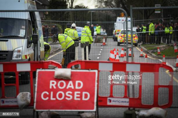 National Grid engineers work on a gas pipe after a sinkhole approximately 35ft wide and 20ft deep appeared under part of a home and the road in...