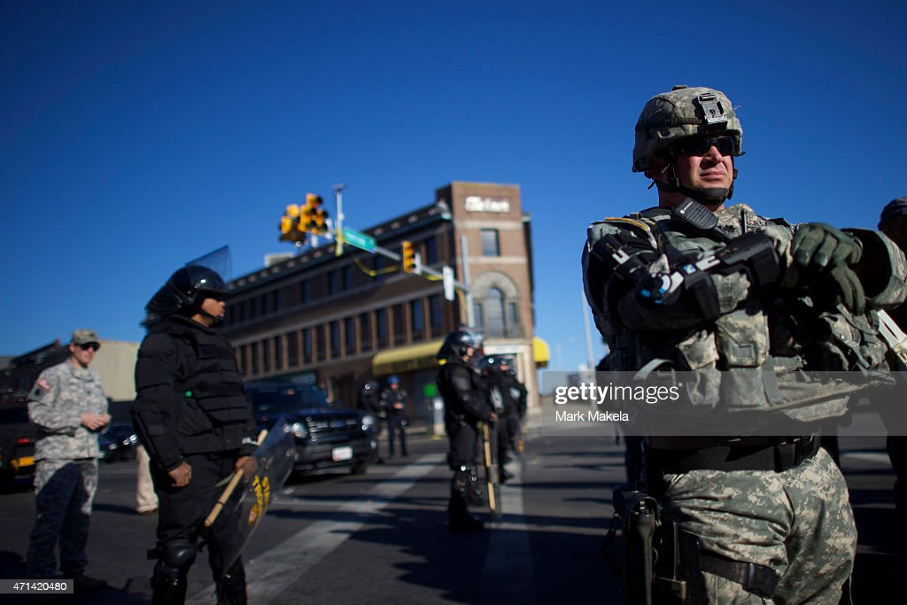 National Guard and Baltimore police dressed in riot gear line the street the morning after citywide riots following the funeral of Freddie Gray on...