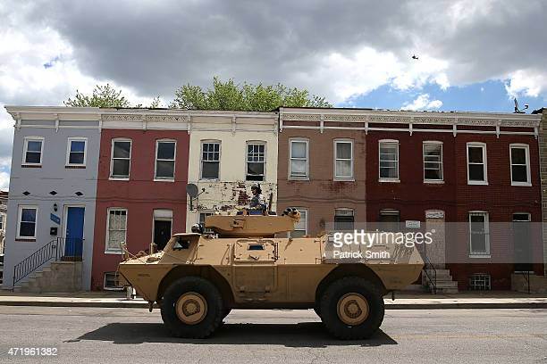 National Guard armored vehicles drive near the Gilmor Houses housing project a day after Baltimore authorities released a report on the death of...