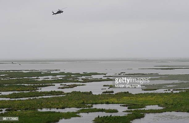 A National Guard helicopter flies over the fragile wetlands in the path of spreading of oil from the BP Deepwater Horizon platform disaster off the...