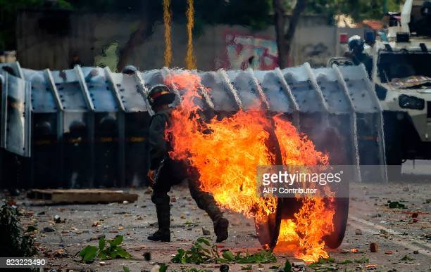 A national Guard member walks away from a fire during an antigovernment protest in Caracas on July 26 2017 Venezuelans blocked off deserted streets...
