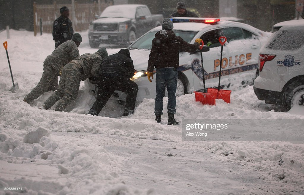 National Guard members and other people help to push a police car which got stuck in the snow on January 23 2016 in Washington DC Heavy snow...