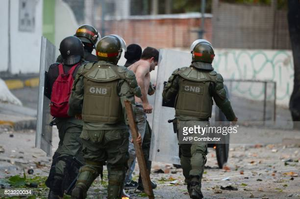 National Guard personnel in riot gear arrest an opposition demonstrator during clashes ensuing an antigovernment protest in Caracas on July 26 2017...