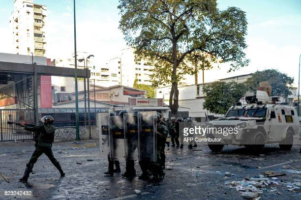 National Guard personnel in riot gear supported by a riot control vehicle prepare to charge on opposition demonstrators during an antigovernment...