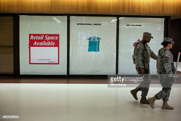National Guard personnel walk past an empty storefront at the Port Authority Bus Terminal in New York US on Friday Dec 12 2014 The Port Authority of...