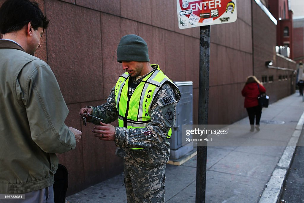 A National Guard soldier checks identification near a roadblock near the scene of a twin bombing at the Boston Marathon on April 16, 2013 in Boston, Massachusetts. The twin bombings, which occurred near the marathon finish line, resulted in the deaths of three people while hospitalizing at least 128. The bombings at the 116-year-old Boston race, resulted in heightened security across the nation with cancellations of many professional sporting events as authorities search for a motive to the violence.