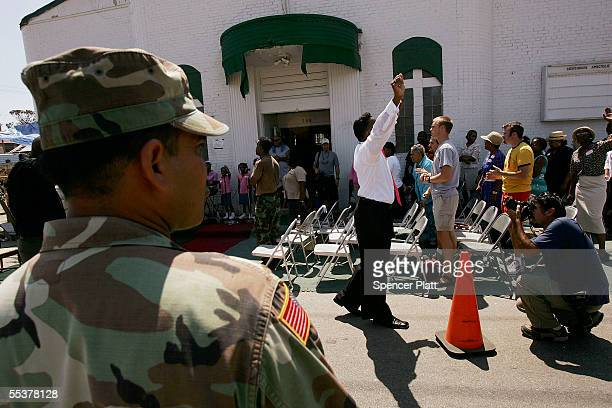 National Guard soldier watches over a Sunday service outside of the Lighthouse Apostolic Church which was damaged by Hurricane Katrina September 11...