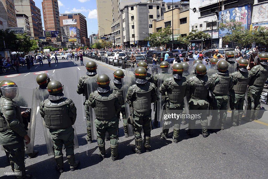 National Guard soldiers in riot gear form a line to block a protest march of pposition students demanding to know the real situation of President Hugo Chavez's health, in Caracas on March 3, 2013. Chavez is still in charge and mulling political, social and economic policies even as he receives a new round of chemotherapy, his vice president said Saturday.. AFP PHOTO / Leo RAMIREZ