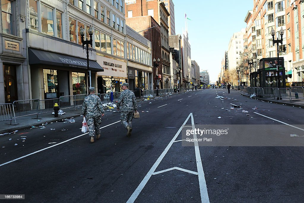 National Guard soldiers walk near the scene of a twin bombing at the Boston Marathon on April 16, 2013 in Boston, Massachusetts. The twin bombings, which occurred near the marathon finish line, resulted in the deaths of three people while hospitalizing at least 128. The bombings at the 116-year-old Boston race, resulted in heightened security across the nation with cancellations of many professional sporting events as authorities search for a motive to the violence.