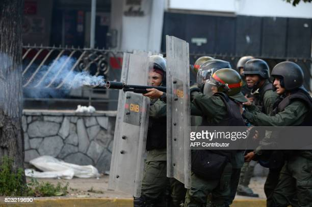 A National Guard trooper fires a tear gas grenade at opposition demonstrators during clashes ensuing an antigovernment protest in Caracas on July 26...