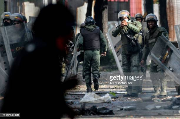 A National Guard trooper in riot gear aims his shotgun at opposition demonstrators during clashes ensuing an antigovernment protest in Caracas on...