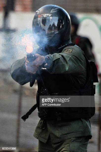 A National Guard trooper in riot gear fires his shotgun at opposition demonstrators during clashes ensuing an antigovernment protest in Caracas on...