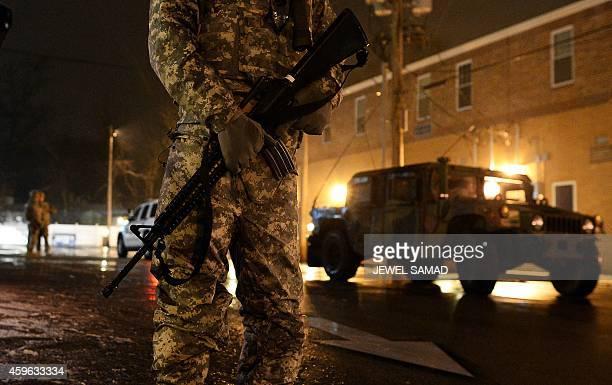 A National Guard trooper keeps vigil near the police station in Ferguson Missouri on November 26 2014 The streets of Ferguson were decidedly calmer...