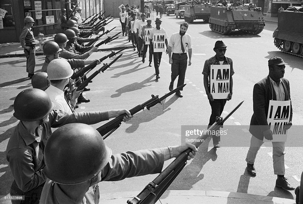 US National Guard troops block off Beale Street as Civil Rights marchers wearing placards reading 'I AM A MAN' pass by on March 29 1968 It was the...
