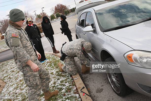 National Guard troops help stranded motorists after they got a flat tire on their way to pick up a family member for Thanksgiving dinner November 27...