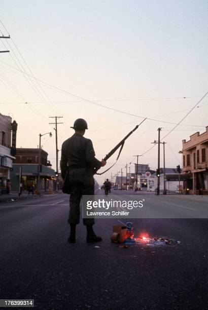 A National Guardsman stands watch on a street in the Watts neighborhood after the declaration of Marshall Law due to ongoing riots Los Angeles...