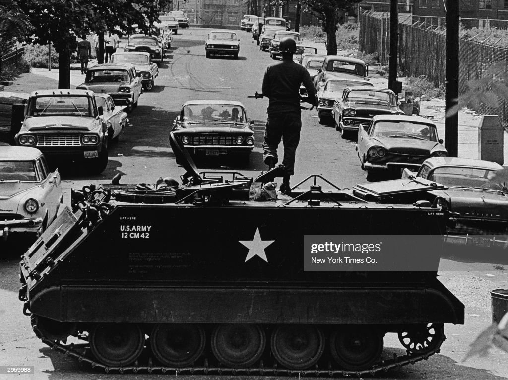 A National Guardsmen stands with a rifle atop a personnel carrier vehicle, blocking traffic leaving the area during race riots, Newark, New Jersey, July 16, 1967.