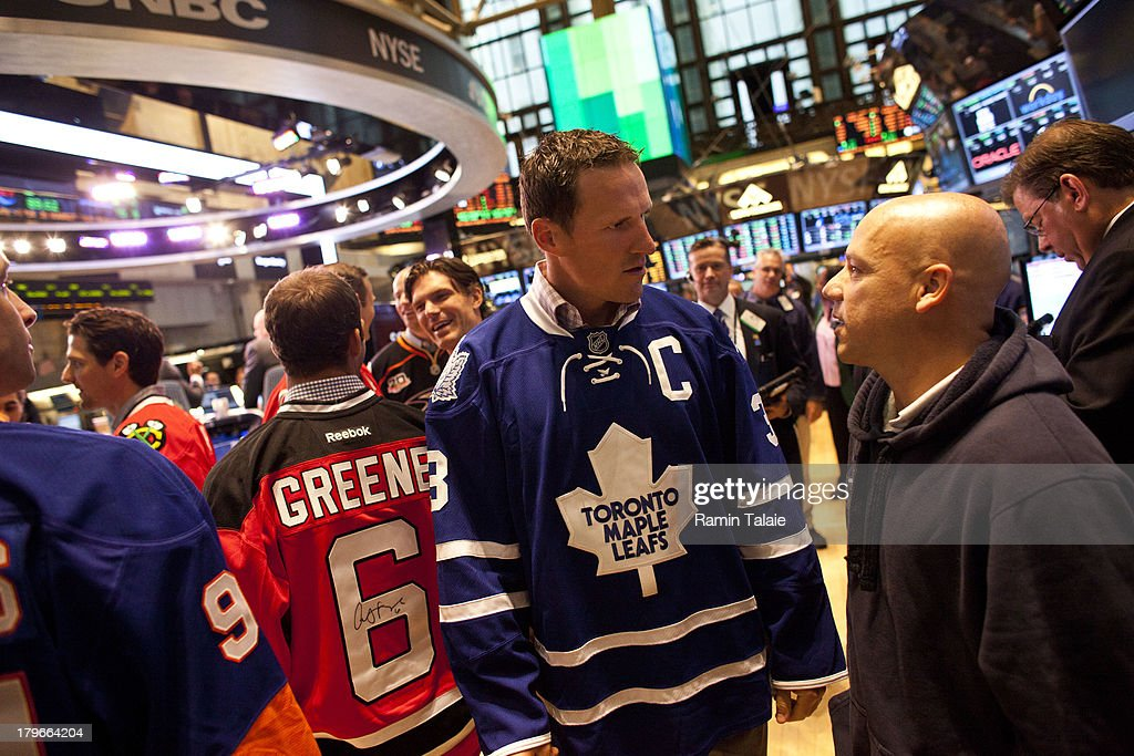 National Hockey League (NHL) player <a gi-track='captionPersonalityLinkClicked' href=/galleries/search?phrase=Dion+Phaneuf&family=editorial&specificpeople=545455 ng-click='$event.stopPropagation()'>Dion Phaneuf</a> of the Toronto Maple Leafs speaks with a trader on the floor of the New York Stock Exchange (NYSE) after ringing the opening bell on September 6, 2013 in New York City. NHL is celebrating the start of upcoming 2013-12 season featuring six outdoor hockey games.