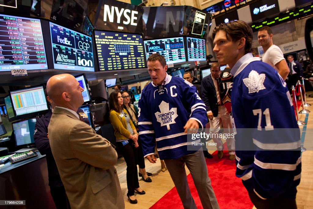 National Hockey League (NHL) players <a gi-track='captionPersonalityLinkClicked' href=/galleries/search?phrase=Dion+Phaneuf&family=editorial&specificpeople=545455 ng-click='$event.stopPropagation()'>Dion Phaneuf</a> (C) and David Clarkson (R) of the Toronto Maple Leafs, speak with traders on the floor of the New York Stock Exchange (NYSE) after ringing the opening bell on September 6, 2013 in New York City. NHL is celebrating the start of upcoming 2013-12 season featuring six outdoor hockey games.