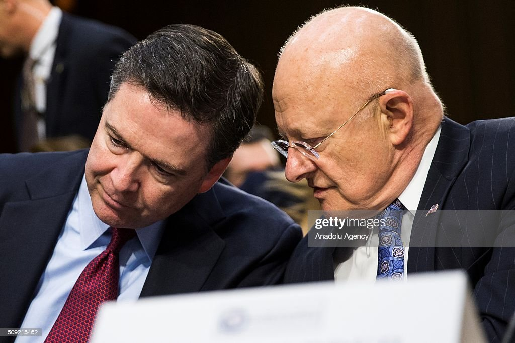 National Intelligence James Clapper (R) whispers to FBI Director James Comey during a Senate Intelligence Committee hearing in Washington, USA on February 9, 2016.