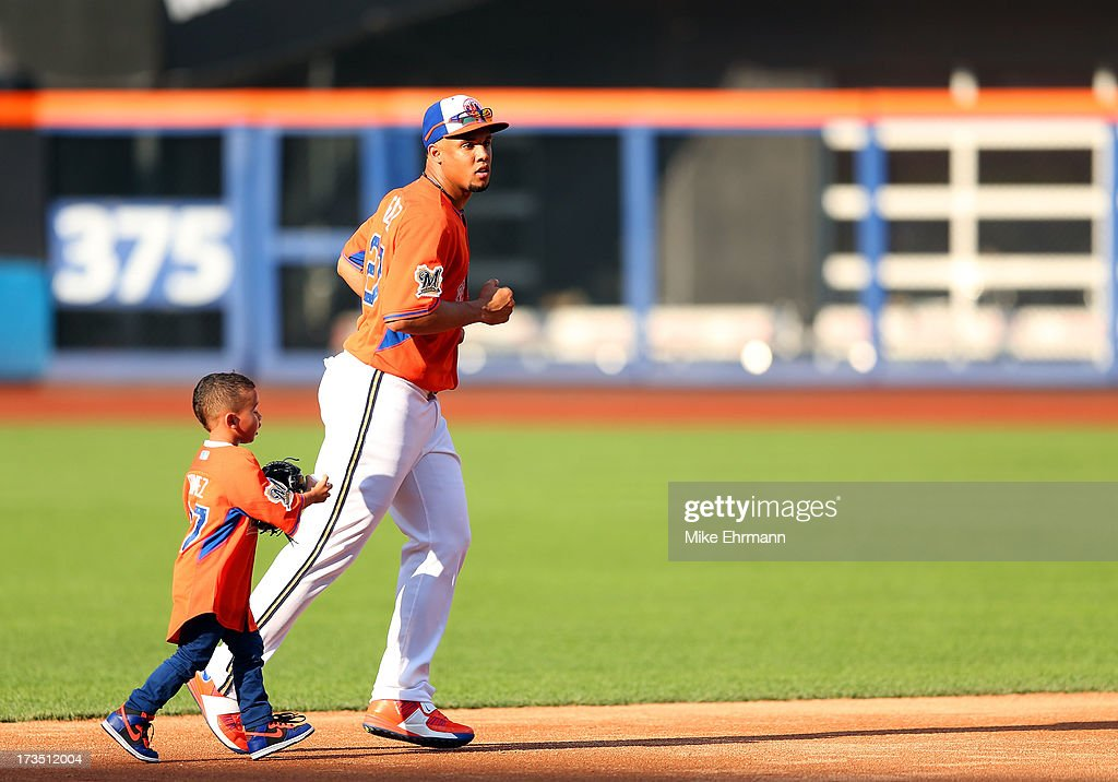 National League All-Star Carlos Gomez of the Milwaukee Brewers and his son take part in the Gatorade All-Star Workout Day on July 15, 2013 at Citi Field in the Flushing neighborhood of the Queens borough of New York City.