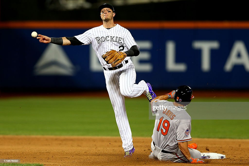 National League All-Star Troy Tulowitzki #2 of the Colorado Rockies turns a double play over American League All-Star Chris Davis #19 of the Baltimore Orioles in the fourth inning during the 84th MLB All-Star Game on July 16, 2013 at Citi Field in the Flushing neighborhood of the Queens borough of New York City.