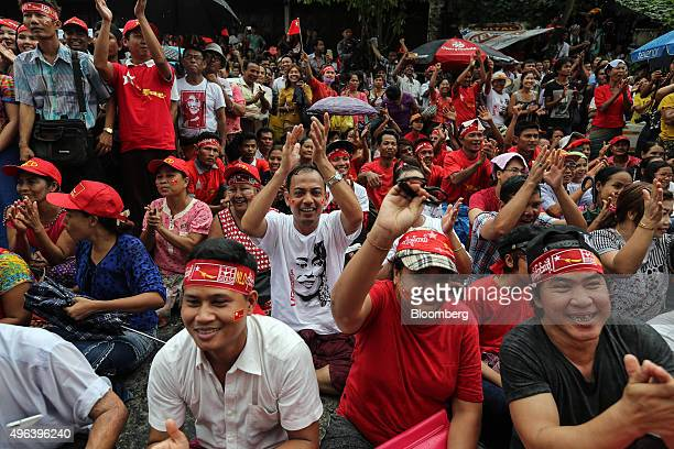 National League for Democracy party supporters celebrate as they watch a screen showing election results outside the party headquarters in Yangon...